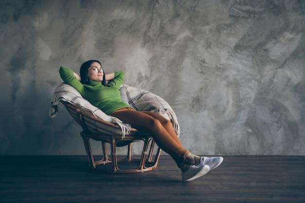 오렌지 바지 고립 된 회색 벽 콘크리트 배경에 창 밖을보고 안락의 자에 나머지에 누워 쾌활 한 비즈니스 아가씨의 전체 길이 신체 크기 사진