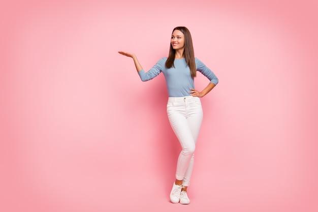 Фотография в полный рост веселой уверенной и позитивной подруги, держащей руку на талии, держащей объект, показывающая пустое пространство на изолированном пастельном цветном фоне