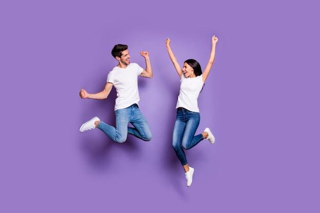 쾌활한 흥분된 황홀한 긍정적 인 미친 사람들의 전체 길이 신체 크기 사진 흰색 신발 티셔츠 청바지 데님 갈색 머리 점프 비명 예 절연 파스텔 색상 보라색 배경