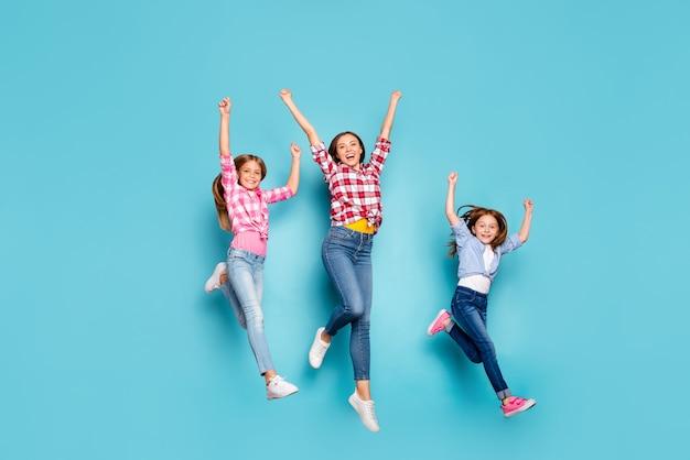 Фотография в полный рост веселой дружелюбной белой семьи, наслаждающейся победой в соревнованиях по бегу в стиле пин-ап, изолированной на синем фоне в джинсах