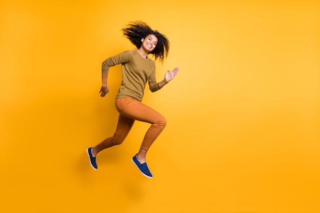 鮮やかな色の背景の上に隔離された空のスペースに向かってジャンプして走っているオレンジ色のズボンのズボンを身に着けている陽気なポジティブな美しい魅力的な魅力的なかわいい女の子の全身サイズの写真