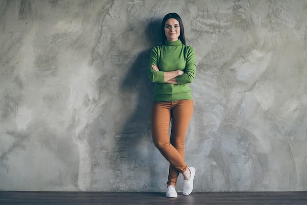 쾌활한 긍정적 인 귀여운 예쁜 좋은 여자의 전체 길이 신체 크기 사진 다리에 자신있게 서 입고 안경 절연 벽 콘크리트 회색 배경