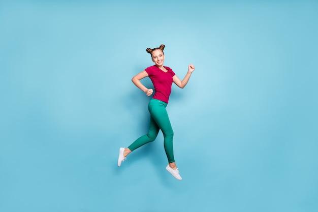 빨간색 티셔츠를 입고 쾌활한 긍정적 인 측면 프로필 소녀의 전체 길이 신체 크기 사진 바지 녹색 격리 된 파스텔 블루 컬러 벽에 점프 판매를 위해 이빨 웃고