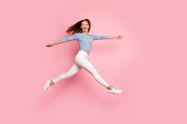 Фотография в полный рост веселой боковой профиль сумасшедшей бегущей прыгающей подруги, выражающей эмоции на изолированном пастельном фоне лица
