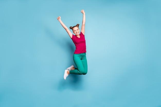 파스텔 블루 컬러 벽에 고립 된 우승 대회에서 기뻐하는 바지 바지 녹색을 입고 밝은 흰색 갈색 머리 머리 여자 친구의 전체 길이 신체 크기 사진