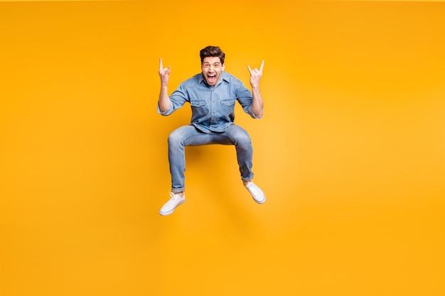 Фотография в полный рост кричащего парня с рогатыми пальцами в кроссовках, показывающего, как скальные рогатые пальцы подписывают прыжки, изолированные на стене ярких цветов