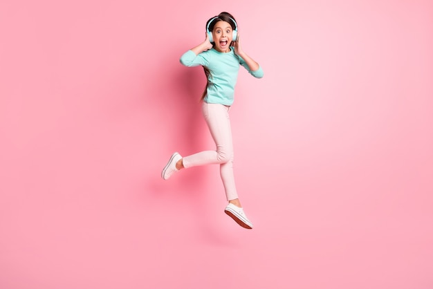 Сумасшедшая маленькая латиноамериканская девочка в полный рост, вскакивающая и кричащая в наушниках, изолированная на розовом фоне