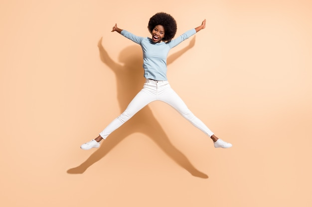 베이지 색 배경에 고립 된 척 별 점프 어두운 피부와 곱슬 재미 있는 여자의 전체 길이 신체 크기 사진