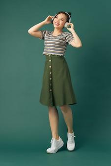 녹색 배경에 고립되어 있는 동안 디스코에서 자신을 상상하는 춤추는 소녀의 전신 크기 사진