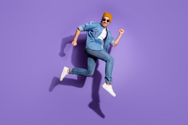 鮮やかな紫色の背景に分離された売上高に到達しようとスポーツランニングを楽しんでいる恍惚とした喜びの大喜びの男の全身サイズの写真