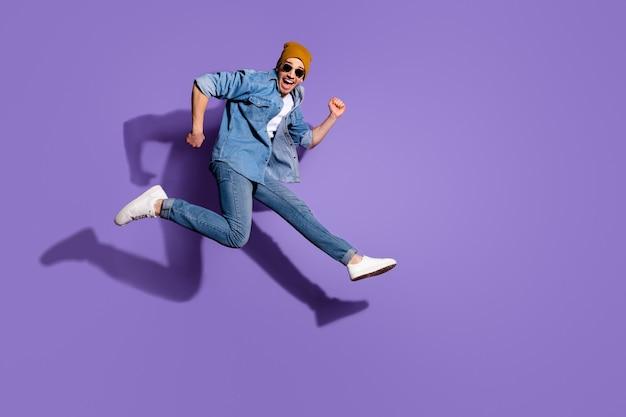 Фотография в полный рост возбужденного, жизнерадостного экстатического красивого удивленного изумленного изумленного парня, бегущего к магазину со скидкой, изолированному на ярком фиолетовом фоне