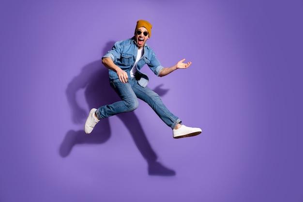 紫色の鮮やかな色の背景の上に分離されたジーンズデニムトレンディなスタイリッシュなジーンズを身に着けている高速演奏ギターを実行してジャンプアップ興奮したギタリストの全身サイズの写真