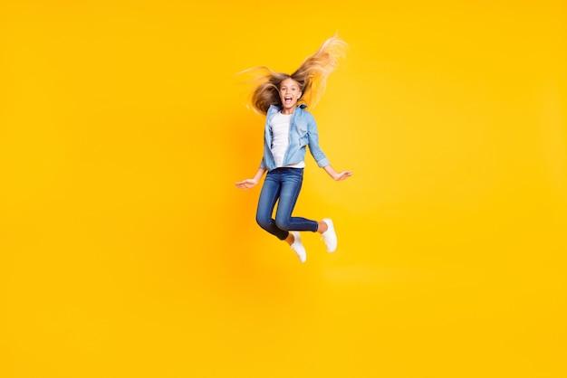 Фотография в полный рост счастливой жизнерадостной девушки с длинными светлыми волосами, прыгающая высоко, крича, изолирована на ярко-желтом цветном фоне