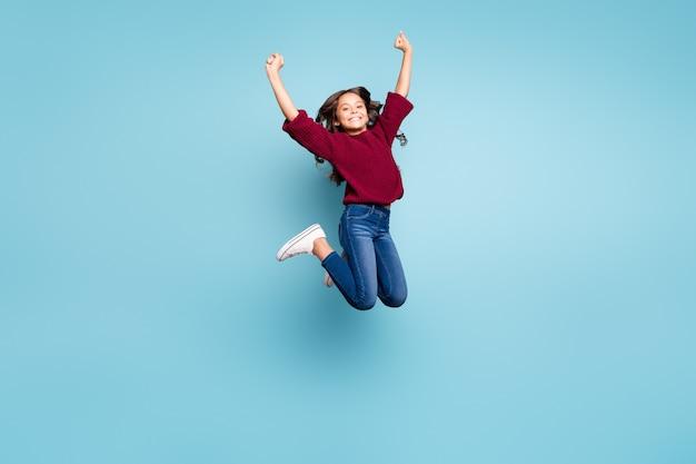 Фотография в полный рост позитивной жизнерадостной кудрявой девушки, подпрыгивающей в джинсах, улыбающейся зубастой улыбкой на ярком синем цветном фоне