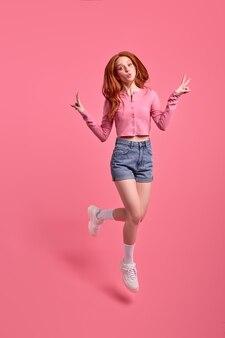 Фотография в полный рост рыжей женщины, прыгающей, показывая vsign, изолированную на ярко-розовом цветном фоне, студийный портрет молодой женщины в розовой рубашке и джинсовых джинсах, выглядящей счастливой