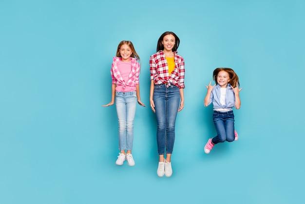 青い背景で隔離されている間、ジーンズのデニムを着てジャンプして自由な時間を過ごしている素敵な白いカジュアルなピンナップ家族を喜んでの全身サイズの写真