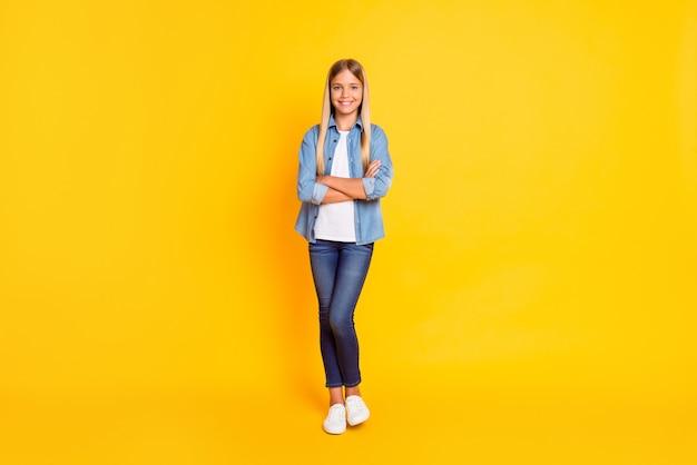 Фотография школьницы с прямыми светлыми волосами в полный рост, скрестив руки, изолирована на ярко-желтом фоне