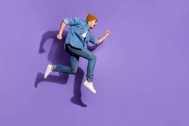 鮮やかな紫色の背景の上に孤立して跳ね上がる割引商品を目指して叫んでいる高速の速いランニングマンの全身サイズの写真