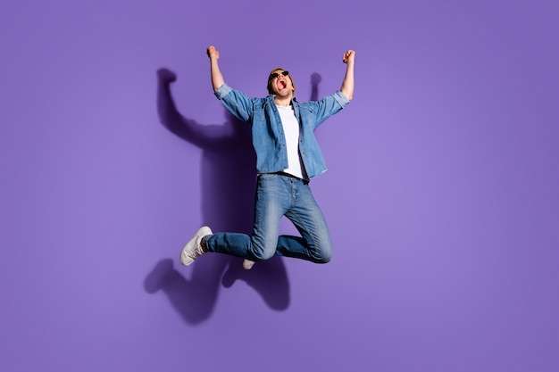 紫色の鮮やかな色の背景の上に分離された販売のためにジャンプする彼の勝利に恍惚とした大喜びの男を喜んで叫んで叫んでいる全身サイズの写真