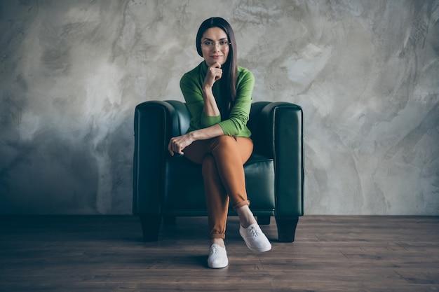 콘텐츠 관리자 격리 회색 벽 컬러 콘크리트 배경으로 일하고 오렌지 바지 흰색 신발을 입고 잠겨있는 관심이 웃는 즐거운 행복한 여자 앉아의 전체 길이 신체 크기 사진