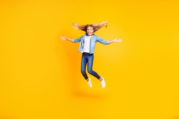 Фотография в полный рост улыбающейся довольной маленькой девочки с длинными волосами, подпрыгивающей и радостно аплодирующей, изолированной на ярко-желтом цветном фоне