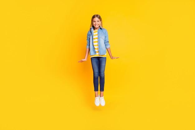 Фотография в полный рост улыбающейся застенчивой девушки со светлыми волосами, высоко прыгающая, держа руки вдоль тела, изолированные на ярко-желтом цветном фоне