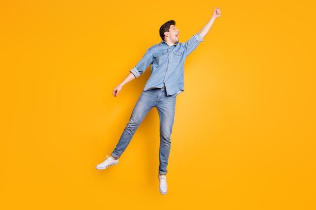 Фотография в полный рост стильного модного мужчины, уносимого с зонтиком порывом сильного ветра, изолированной яркой цветной стеной