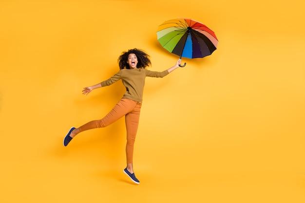 생생한 노란색 배경 위에 절연 오렌지 바지 바지 신발을 입고 우산을 날고 물결 모양의 쾌활한 귀여운 멋진 매력적인 예쁜 여자 친구의 전체 길이 신체 크기 사진