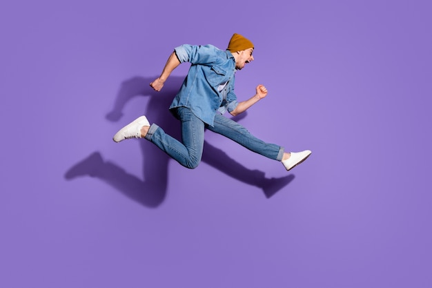 Full length body size photo of shouting urgent hurrying screaming side profile guy aspiring to buying discounted goods wearing denim jacket footwear isolated over vivid purple color background