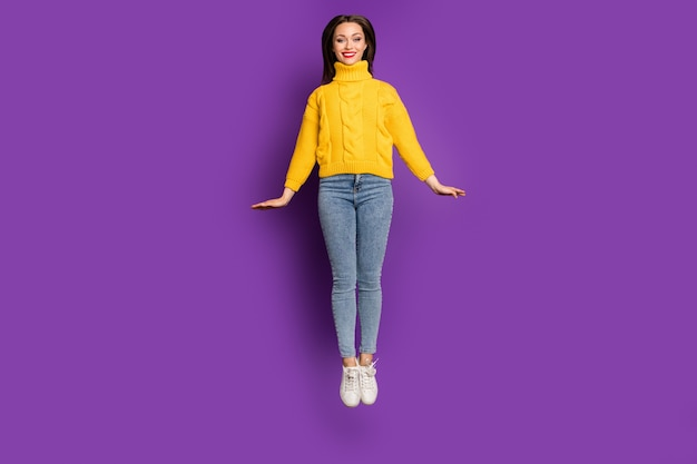 Full length body size portrait of cheerful positive cute pretty nice woman in jeans denim smiling toothily jumping up .