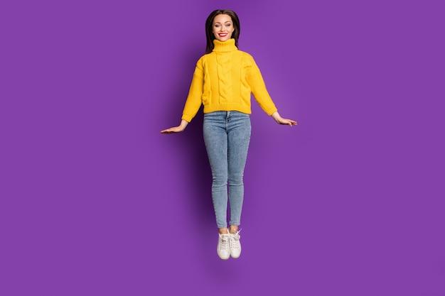 청바지 데님에 쾌활한 긍정적 인 귀여운 꽤 좋은 여자의 전체 길이 몸 크기 초상화는 이빨 점프 웃고.