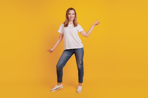 Full length body size of positive glad girl dance enjoy dreamy mood on yellow background