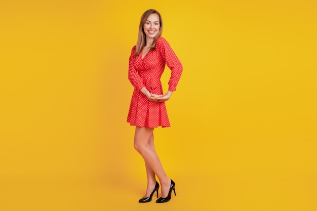 Full length body size of positive glad girl dance funny pose look camera on yellow wall