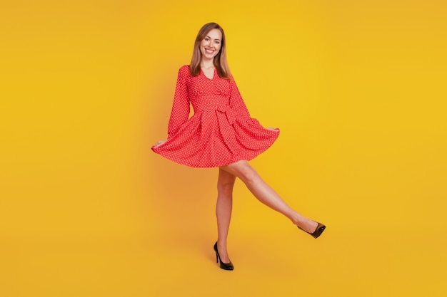 Full length body size of positive glad girl dance hold red skirt on yellow wall