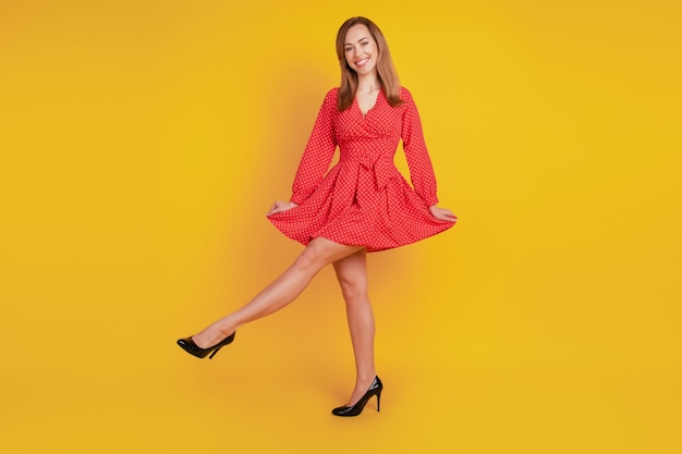 Full length body size of positive glad girl dance on yellow background wear red fancy dress