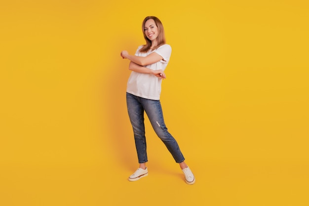 Full length body size of positive glad girl dance on yellow wall