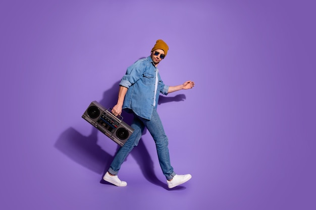 보라색 밝은 색상 배경 위에 절연 디스코텍에가는 손으로 사운드 레코더를 들고 평온한 이동 매력적인 잘 생긴 남자의 전체 길이 신체 크기 프로필 측면 사진