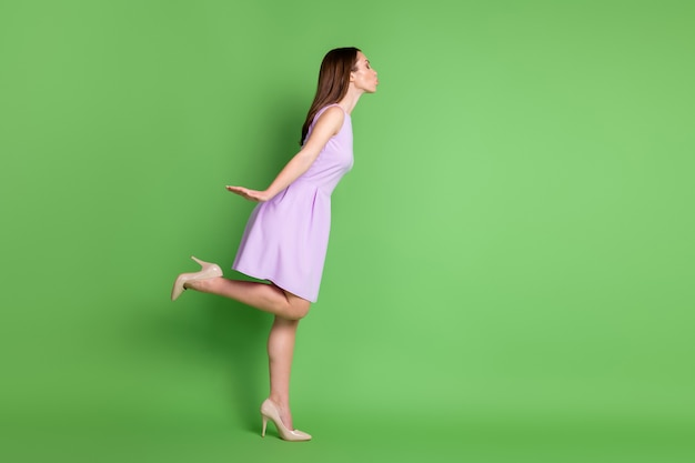 Full length body size profile side view of her she nice-looking attractive pretty lovely lovable dreamy amorous girl posing sending air kiss 14 february date isolated green color background