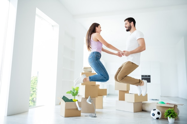 Full length body size profile side view of nice attractive lovely glad cheerful cheery couple jumping having fun holding hands owners property real-estate at light white interior house apartment