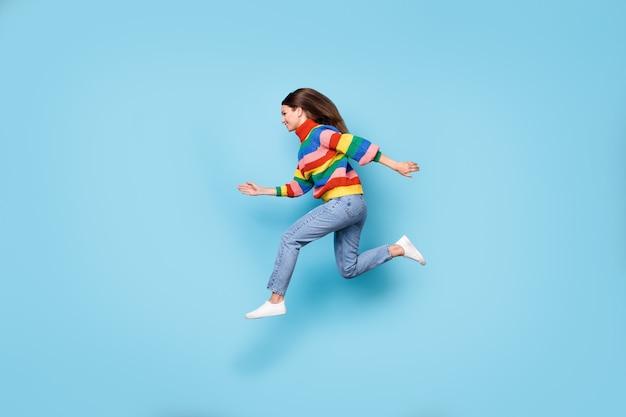 Полноразмерный профиль размера тела, вид сбоку, она красивая привлекательная энергичная веселая девушка, прыгающая, бегущая, быстрая скидка, изолированный синий пастельный цвет фона