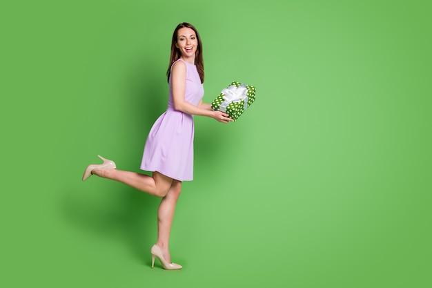 Полный размер тела профиль вид сбоку она красивая привлекательная довольно очаровательная элегантная веселая веселая девушка позирует, держа в руках подарочную коробку лучшая продажа изолированный зеленый цвет фона
