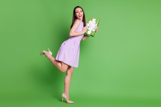 Полный размер тела профиль вид сбоку она красивая привлекательная довольно элегантная веселая веселая девушка позирует, держа в руках пунктирную подарочную коробку, наслаждаясь позированием изолированного зеленого цвета фона