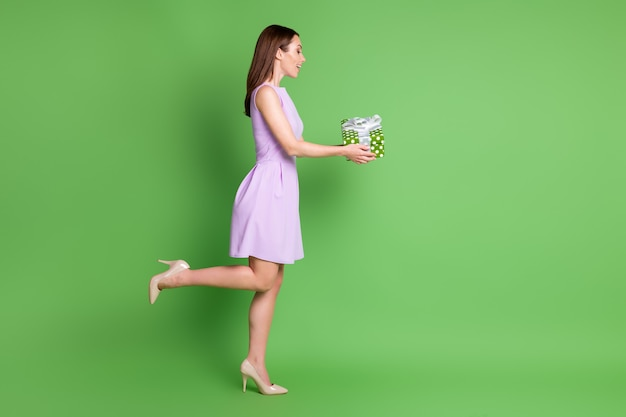 Полный размер тела профиль вид сбоку она красивая привлекательная довольно милая веселая веселая радостная девушка позирует, держа в руках подарочную коробку с поздравлениями, изолированный зеленый цвет фона
