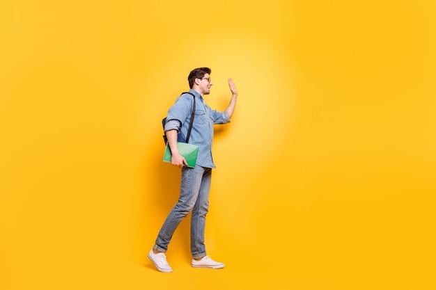 明るい鮮やかな輝きの鮮やかな黄色の壁の上に隔離された彼の素敵な魅力的な陽気な陽気なフレンドリーな男が手を振っている会議の仲間を歩いている全身サイズのプロファイルの側面図