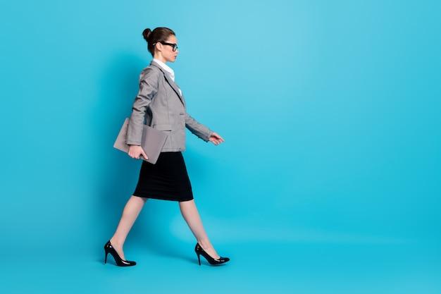 Полноразмерный профиль размера тела, вид сбоку красивой стильной леди-тренера с ноутбуком, изолированной на ярко-синем цветном фоне