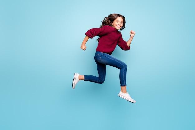 파란색 벽을 뛰어 넘는 전체 길이 신체 크기 측면 프로필 소녀