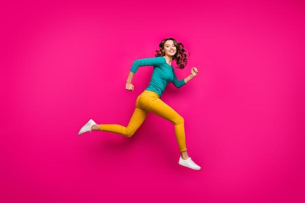쾌활한 긍정적 인 귀여운 좋은 여자의 전체 길이 신체 크기 측면 프로필 사진 곱슬 물결 모양의 흰색 신발 절연 핑크 생생한 컬러 배경 점프 실행