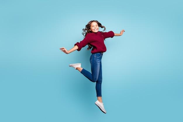 Полная длина тела размер бокового профиля фотография веселой позитивной улыбающейся зубастой сияющей девушки, танцующей как балерина, вьющиеся волнистые прыжки, изолированный яркий синий цвет фона