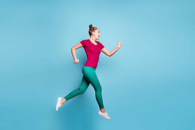 Фото сбоку в полный рост, жизнерадостная стремящаяся девушка спешит и прыгает на продажу, изолированная на стене пастельно-синего цвета