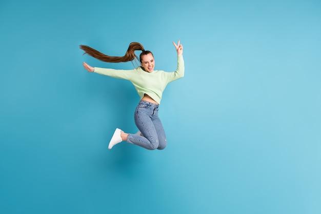 Фотография сбоку в полный рост прыгающей девушки с длинными волосами, показывающая v-образный знак на ярком синем фоне